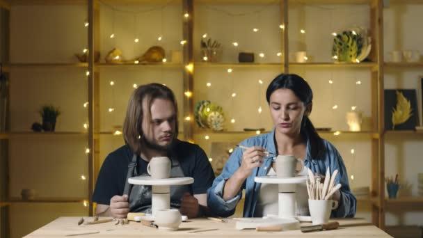 Mann und Frau beim Töpfern. Sie stellt Keramikbecher her