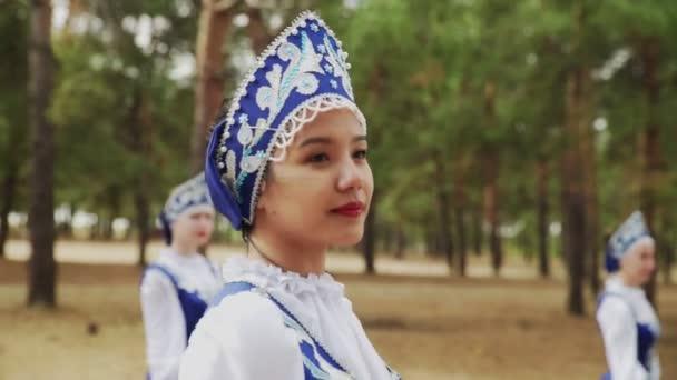 Zblízka šest mladých žen tančí ruské tradiční tance v letním lese
