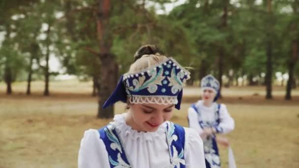 Zblízka mladé krásné ženy v modré rusky Tradiční lidové kostýmy tančí v letním lese