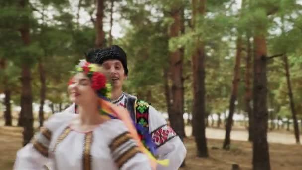 Zblízka páry v tradičních kostýmech tančí ukrajinské národní tance