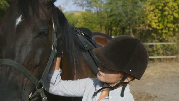 Žena jezdec v jezdeckém oblečení a helma hladí svého koně a dívá se do kamery