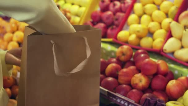 Close up of woman in yellow coat puts red apples into a paper bag at market