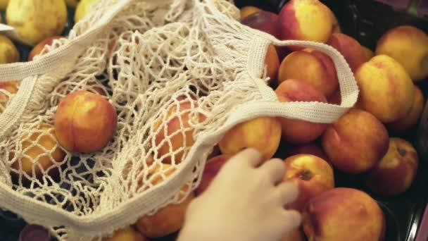 Közelkép nő hátsó pulóver tesz friss őszibarack string bag a piacon