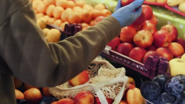 Close up of woman in blue gloves puts red apples into string bag at market