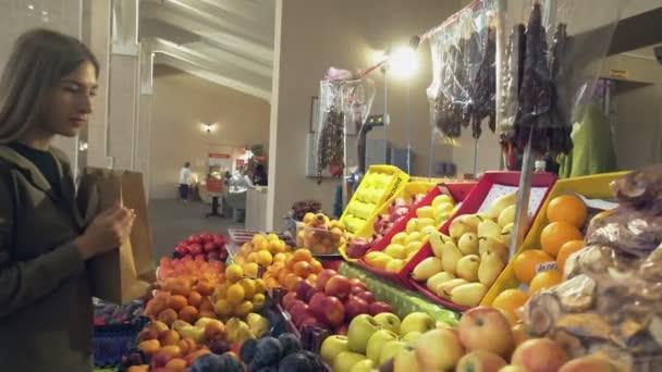 Egy papírzacskós fiatal nő gyümölcsöt választ a bolti polcokon a piacon.