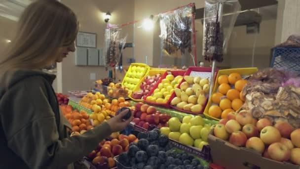 Mladá žena vybírá švestky na prodejních regálech na trhu