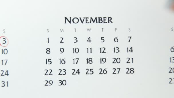 Female hand circle day in calendar date with a red marker. Business Basics Wall Calendar Planner and Organizer. November 3th