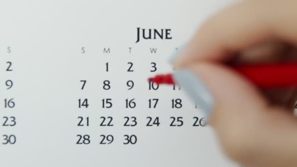 Female hand circle day in calendar date with a red marker. Business Basics Wall Calendar Planner and Organizer. June 9th