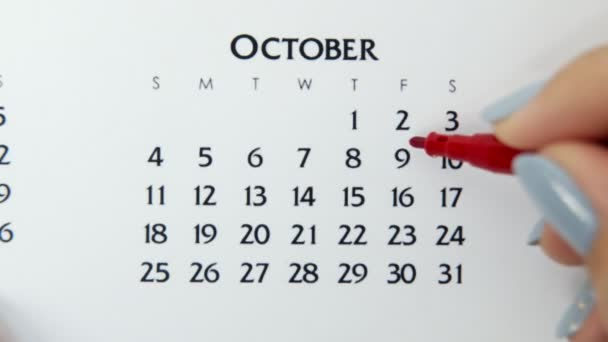 Female hand circle day in calendar date with a red marker. Business Basics Wall Calendar Planner and Organizer. October 9th