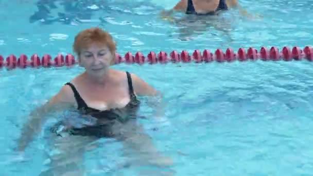 Eine alte Dame trainiert Wassergymnastik im Schwimmbad.