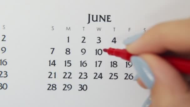 Female hand circle day in calendar date with a red marker. Business Basics Wall Calendar Planner and Organizer. June 10th