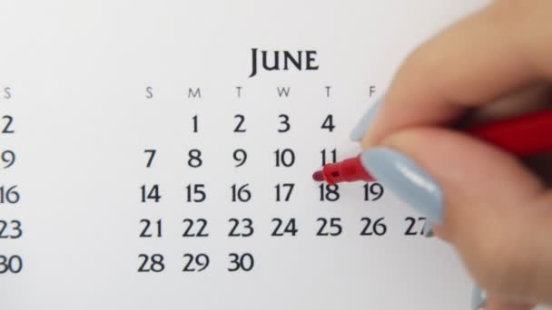 Female hand circle day in calendar date with a red marker. Business Basics Wall Calendar Planner and Organizer. June 18th