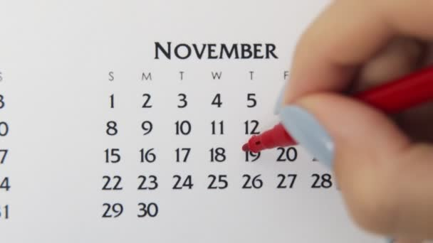 Female hand circle day in calendar date with a red marker. Business Basics Wall Calendar Planner and Organizer. November 19th