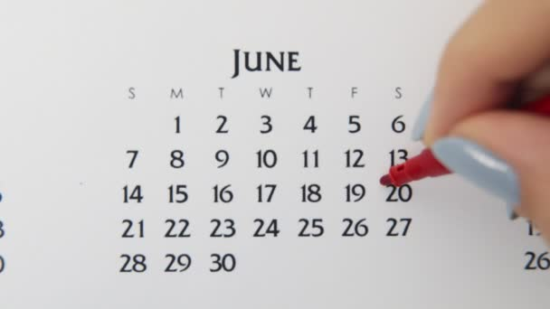 Female hand circle day in calendar date with a red marker. Business Basics Wall Calendar Planner and Organizer. June 20th