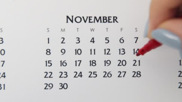 Female hand circle day in calendar date with a red marker. Business Basics Wall Calendar Planner and Organizer. November 21th
