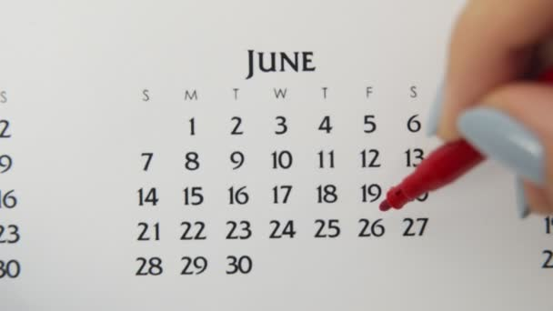 Female hand circle day in calendar date with a red marker. Business Basics Wall Calendar Planner and Organizer. June 26th