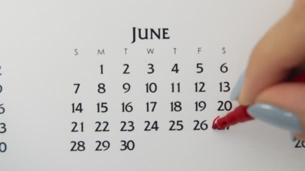 Female hand circle day in calendar date with a red marker. Business Basics Wall Calendar Planner and Organizer. June 27th
