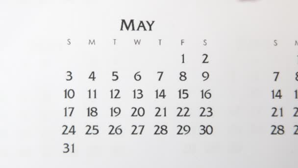Female hand circle day in calendar date with a red marker. Business Basics Wall Calendar Planner and Organizer. May 1th