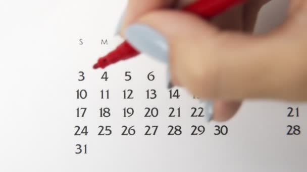 Female hand circle day in calendar date with a red marker. Business Basics Wall Calendar Planner and Organizer. May 3th