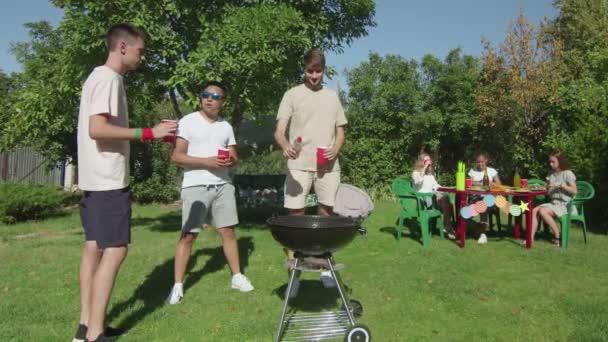Mladí muži vaří lahodné jídlo na grilu, zatímco tři krásné dívky sedí u stolu a krájí zeleninu