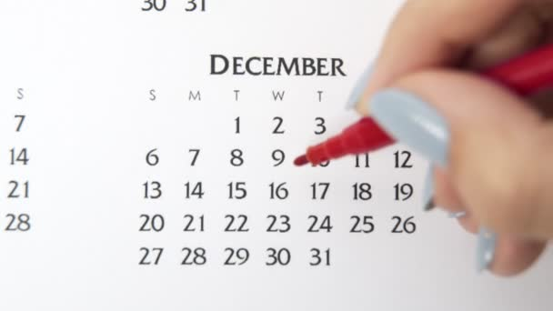Female hand circle day in calendar date with a red marker. Business Basics Wall Calendar Planner and Organizer. December 16th