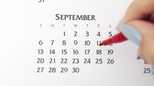 Female hand circle day in calendar date with a red marker. Business Basics Wall Calendar Planner and Organizer. September 18th