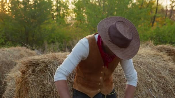 Hezký kovboj pózuje blízko sena na své farmě