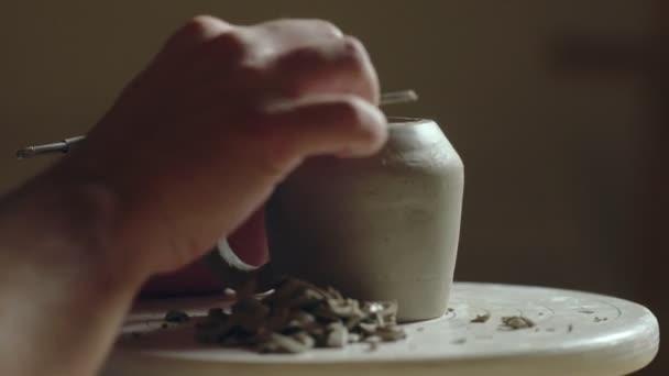 Nahaufnahme des Töpfers mit Werkzeugen zur Herstellung von Keramik Ton Boden der Tasse in Töpferatelier