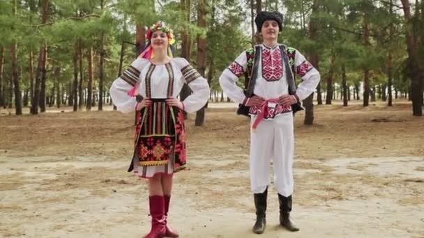 Mladá žena a muž v tradičních kostýmech tančí ukrajinský národní tanec