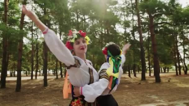 Dvě krásné ženy v tradičních kostýmech tančí Ukrajinské národní tance