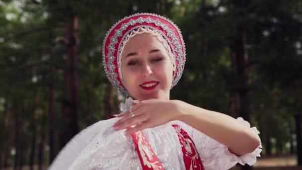 Zblízka mladé ženy tančí červené ruské tradiční tance v letním lese