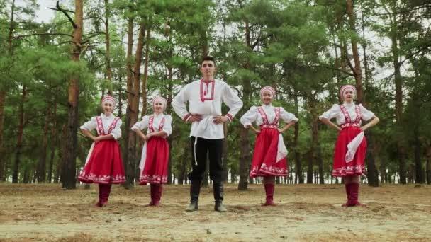 Jeden muž a čtyři mladé ženy tančí ruské tradiční tance v letním lese
