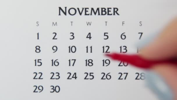 Female hand circle day in calendar date with a red marker. Business Basics Wall Calendar Planner and Organizer. November 9th