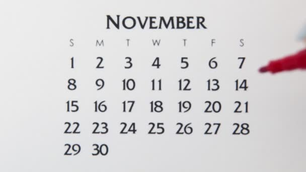 Female hand circle day in calendar date with a red marker. Business Basics Wall Calendar Planner and Organizer. November 14th