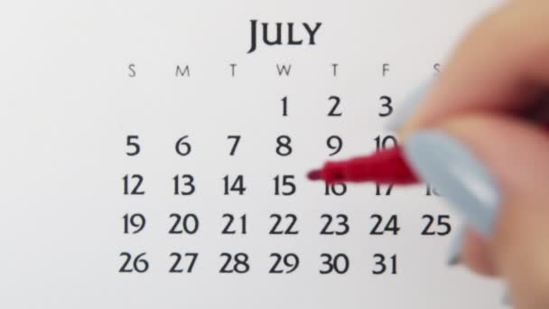 Female hand circle day in calendar date with a red marker. Business Basics Wall Calendar Planner and Organizer. July 15th