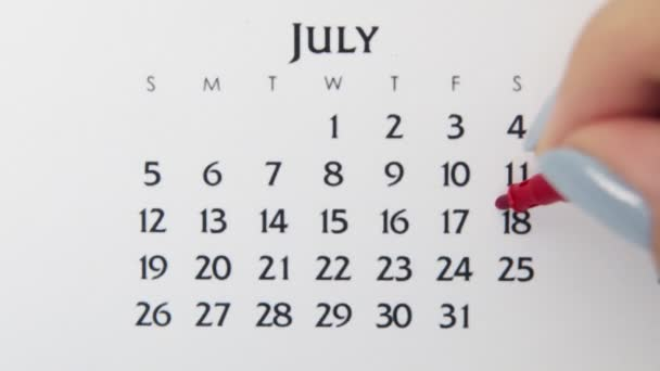 Female hand circle day in calendar date with a red marker. Business Basics Wall Calendar Planner and Organizer. July 18th