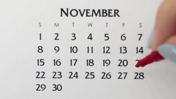 Female hand circle day in calendar date with a red marker. Business Basics Wall Calendar Planner and Organizer. November 28th