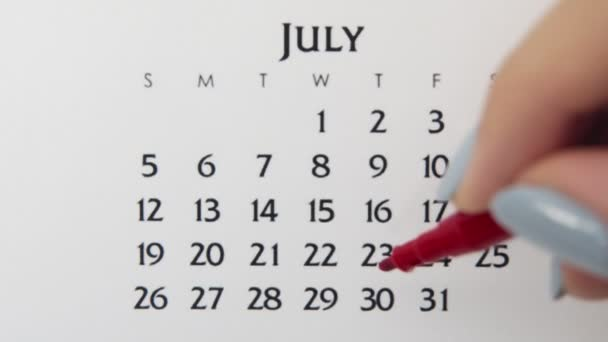 Female hand circle day in calendar date with a red marker. Business Basics Wall Calendar Planner and Organizer. July 30th