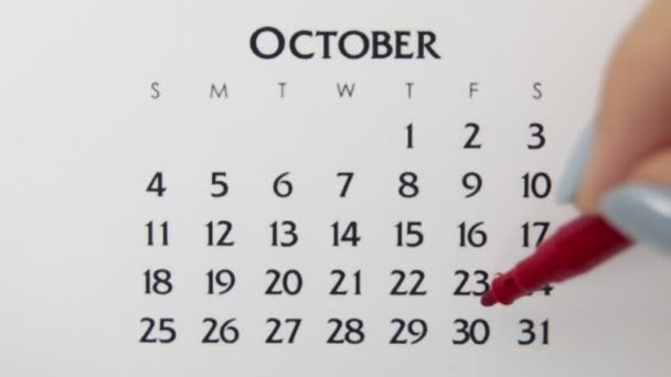 Female hand circle day in calendar date with a red marker. Business Basics Wall Calendar Planner and Organizer. October 30th