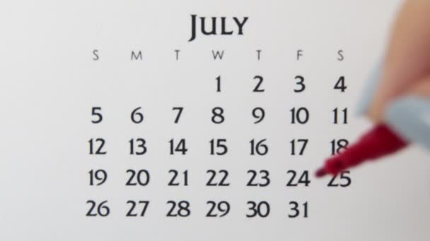 Female hand circle day in calendar date with a red marker. Business Basics Wall Calendar Planner and Organizer. July 31th
