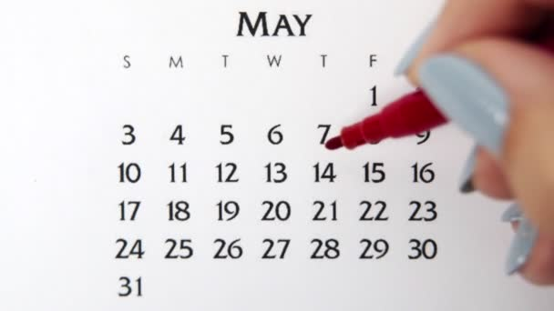 Female hand circle day in calendar date with a red marker. Business Basics Wall Calendar Planner and Organizer. May 14th