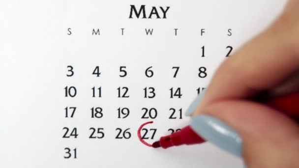 Female hand circle day in calendar date with a red marker. Business Basics Wall Calendar Planner and Organizer. May 27th