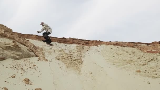 Handsome man sandboards a mountain in desert or sand quarry