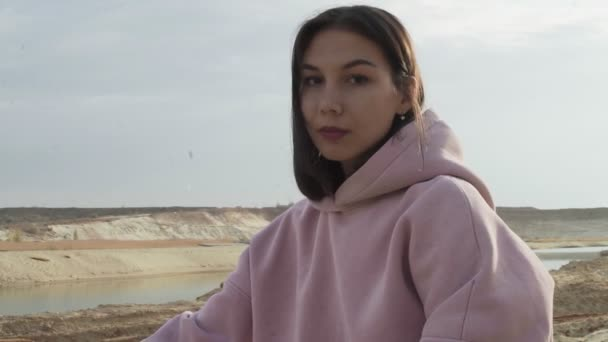 Beautiful fashion model looks at the camera in desert