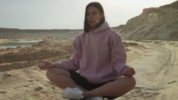 Beautiful fashion model posing and meditation on camera in desert