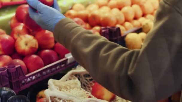 A kék kesztyűs nő közelsége piros almát húszaszsákba tesz a piacon.