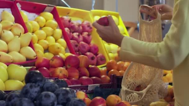 A sárga kabátos nő visszapillantása vörös almát tesz a húszaszsákba a piacon.