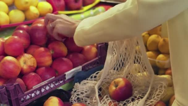 Zadní pohled ženy ve žlutém kabátě dává červená jablka do tašky na trhu