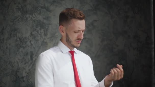 Vousatý pohledný obchodník v bílé košili s červenou kravatou nasazující knoflík manžety na rukáv