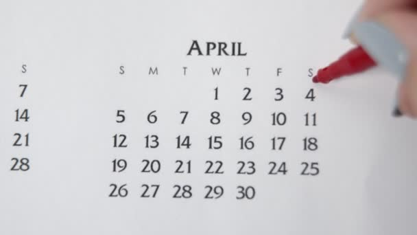 Female hand circle day in calendar date with a red marker. Business Basics Wall Calendar Planner and Organizer. APRIL 4th